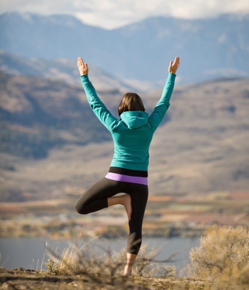 Young active woman doing yoga on mountaintop, facing away from camera.